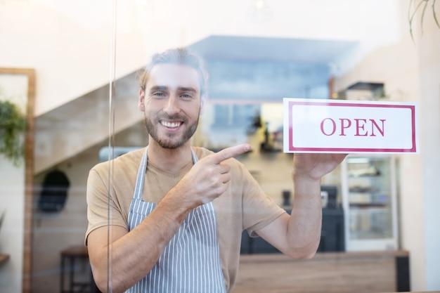 Herzlich willkommen. glücklicher junger bärtiger mann in der schürze, die hinter glas innerhalb des cafés steht, zeigt auf zeichen, das offen am eingang sagt