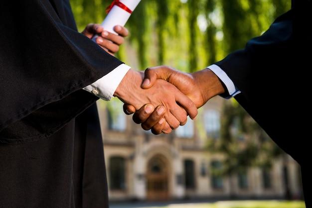 Herzliche glückwünsche! nahaufnahme von zwei männern in abschlusskleidern, die diplome halten und hände schütteln