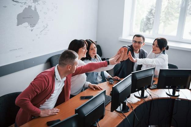 Herzlichen glückwunsch an uns. junge leute, die im call center arbeiten. neue angebote kommen