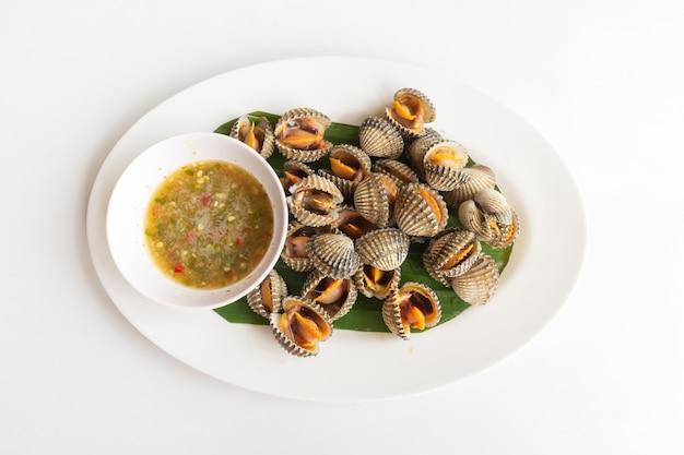 Herzmuschel gedämpft mit meeresfrüchtesauce auf einem weißen tisch thailändisches essen, nahaufnahme von oben.