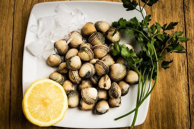 Herzmuscheln, petersilie und eine halbe zitrone auf einer weißen platte mit eis