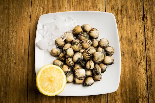 Herzmuscheln und eine halbe zitrone auf einer weißen platte mit eis