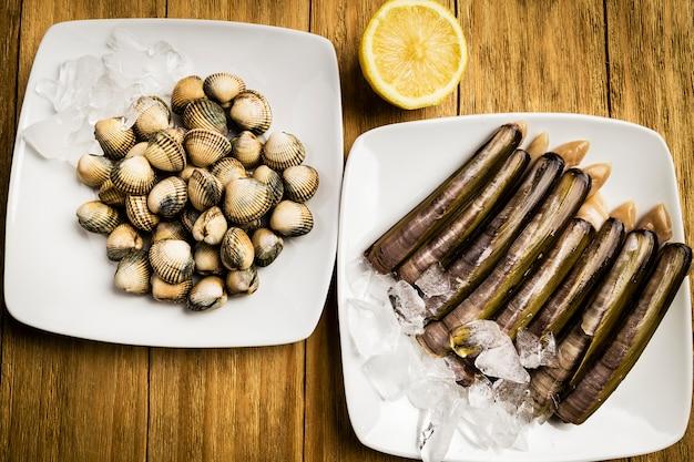 Herzmuscheln und messer, petersilie und eine halbe zitrone auf weißen platten mit eis