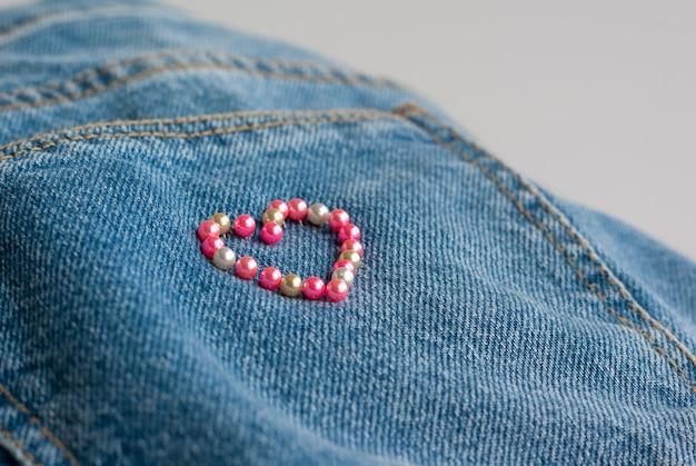 Herzrahmen aus nähnadeln auf jeans-hintergrund