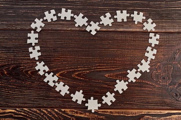 Herzrahmen aus papppuzzles. form des herzens von leeren puzzles auf dunklem hölzernem hintergrund. liebe zum spiel.