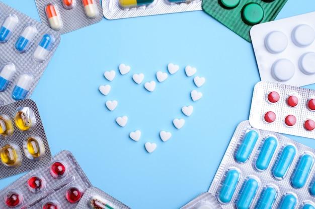 Herzrahmen gemacht von den pillen auf blauer, flacher lage mit raum für text