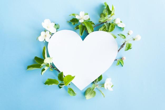 Herzrahmen mit blütenapfel auf blauem hintergrund