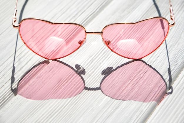 Herzsonnenbrille auf weißem holztisch