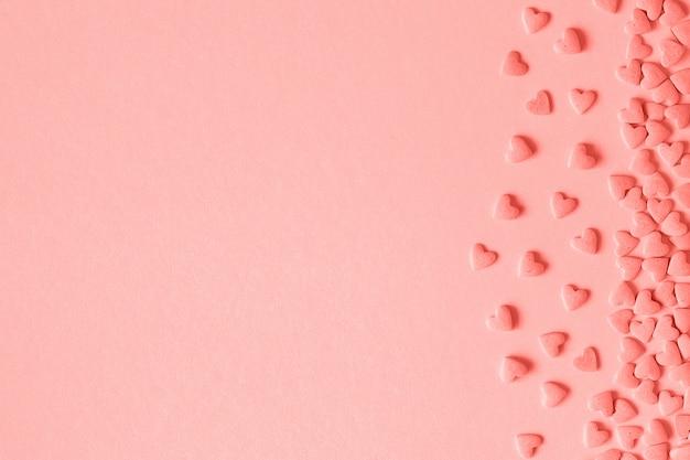 Herzsüßigkeiten besprüht sich gelegen auf der rechten seite auf rosa hintergrund in der koralle getont.