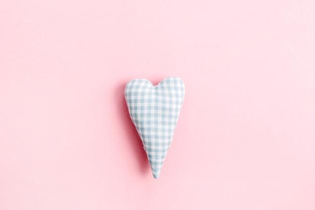 Herzsymbol auf blassrosa hintergrund. flache lage, ansicht von oben liebeskonzept.