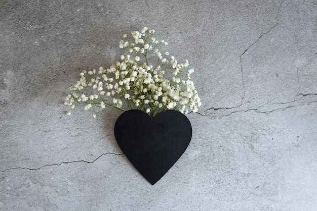 Herzsymbol aus flovers und blättern. männliche hand, die eine letzte blume anhält.
