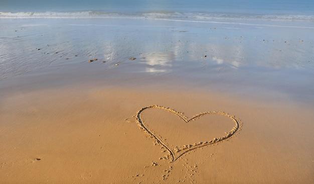 Herzzeichnung auf dem sand vor meer