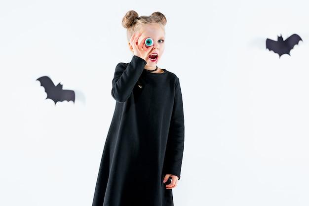 Hexe des kleinen mädchens im schwarzen langen kleid und in den magischen accessoires. halloween