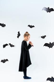 Hexe des kleinen mädchens im schwarzen langen kleid und in den magischen accessoires