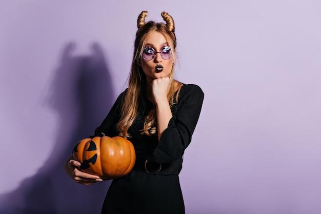Hexe hält großen kürbis. entzückendes blondes mädchen, das sich auf halloween vorbereitet.