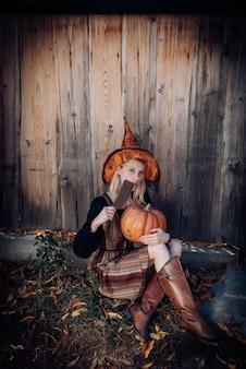 Hexe im halloween-hut posiert im freien hübsche junge frau im hexenkostüm halloween-dekor getöntes bild ...