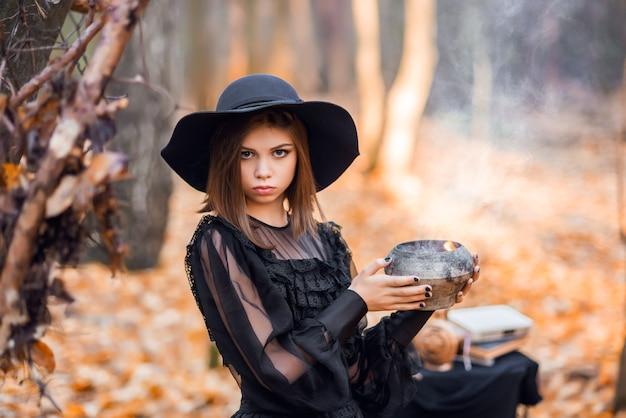 Hexe im herbstwald. porträt eines mädchens in einem schwarzen kleid mit einem trank.