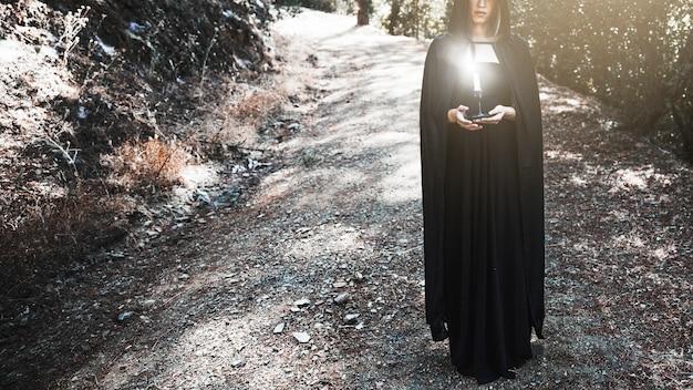 Hexe im umhang, der kerzenständer auf waldweg hält