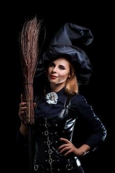 Hexe in einem schwarzen hut mit einem besen