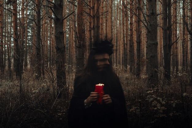 Hexe in einem schwarzen kostüm führt dunkle zauber mit kerzen im wald aus. verschwommenes foto mit unschärfe aufgrund langer belichtungszeit