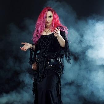 Hexe schafft magie. frau mit roten haaren im hexenkostüm