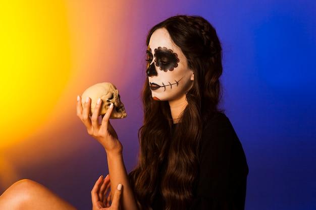 Hexe schaut auf einen schädel