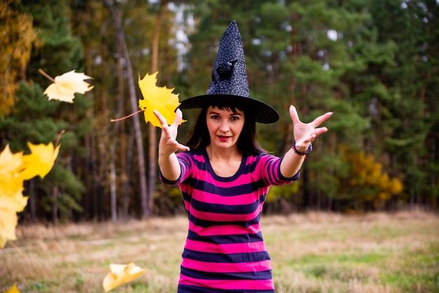 Hexe wirft blätter in den herbstwald. halloween kostümparty zaubererfrau