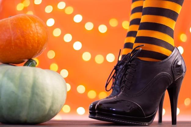 Hexenbeine in gestreiften strümpfen und schuhen mit hohen absätzen mit halloween-kürbissen auf orangefarbenem hintergrund mit bokeh. platz kopieren.