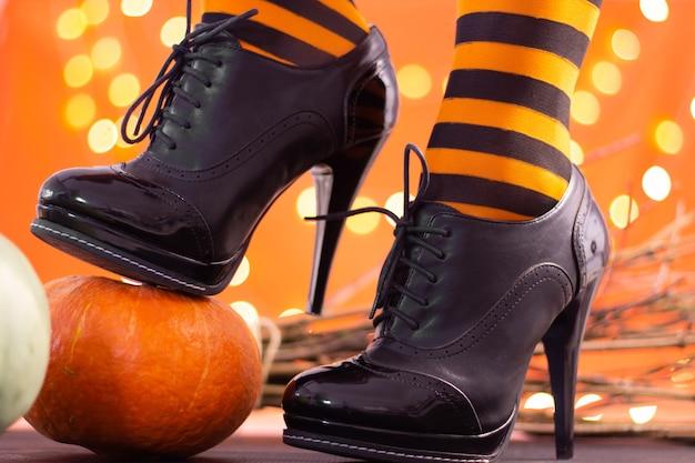 Hexenbeine in gestreiften strümpfen und schuhen mit hohen absätzen mit kürbissen auf orangefarbenem hintergrund, bokeh. halloween. platz kopieren.