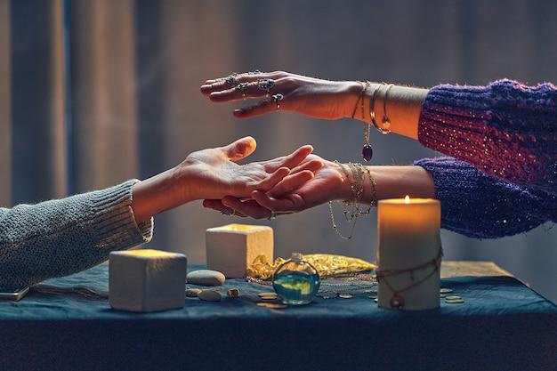Hexenfrau, die über handfläche während des okkulten spirituellen ritus und des wahrsagungsrituals um kerzen und andere magische accessoires buchstabiert. magische illustration