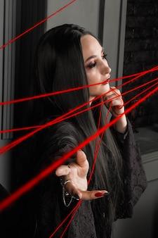 Hexerei, magie. halloween-geschichten beschwört schöne junge sexy hexe über einen roten faden. eine mittelalterliche zauberin durchtrennt die fäden des schicksals.