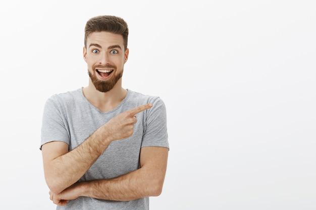 Hey, dieser kopierraum ist großartig. begeisterter und aufgeregter entzückter charmanter männlicher brunet mit bart im grauen t-shirt, der auf die obere rechte ecke zeigt und von coolem objekt fasziniert ist, das breit lächelt
