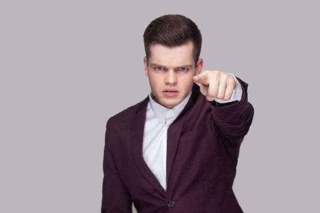 Hey du, das liegt an dir. porträt eines ernsten jungen mannes in violettem anzug und weißem hemd, der mit wütendem gesicht steht, auf die kamera schaut und auf die kamera zeigt. indoor-studioaufnahme, auf grauem hintergrund isoliert.