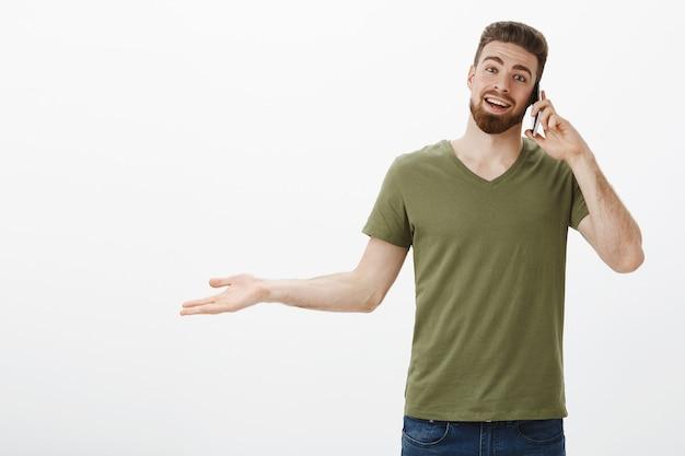Hey, glücklich, einen anruf von deinem kumpel zu erhalten. porträt des erfreuten jungen attraktiven bärtigen kerls, der auf smartphone spricht und hand seitlich ausstreckt, als überrascht und froh, gegen weiße wand zu plaudern