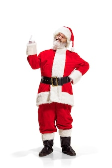 Hey hallo. holly jolly x mas festlichen noel. volle länge des lustigen glücklichen weihnachtsmanns in der kopfbedeckung, im kostüm, im schwarzen gürtel, in den weißen handschuhen, wellen mit armpalme, die im studio über weißem hintergrund stehen