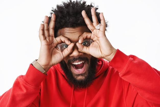 Hey lächle. porträt eines freundlichen und optimistischen, verspielten afroamerikanischen erwachsenen mit bart, ringen und afro-frisur, der eine brille trägt, die eine gute geste auf den augen zeigt und breit über die graue wand lächelt