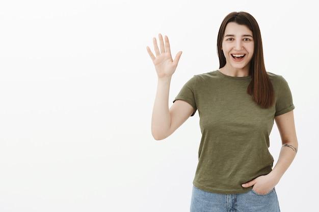 Hey, so schön dich zu treffen. porträt der freundlichen und aufgeregten aufrichtigen aufgeschlossenen frau im t-shirt, das hey als verzicht auf hallo und hallo geste sagt, freunde begrüßt und lächelt