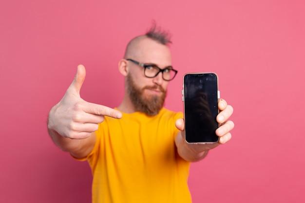 Hey was neues. glücklicher europäischer bärtiger kerl, der sein handy mit schwarzem leerem bildschirm auf rosa zeigt