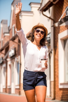 Hi! schöne junge frau mit hut und sonnenbrille, die jemandem winkt und lächelt, während sie durch die straße geht?