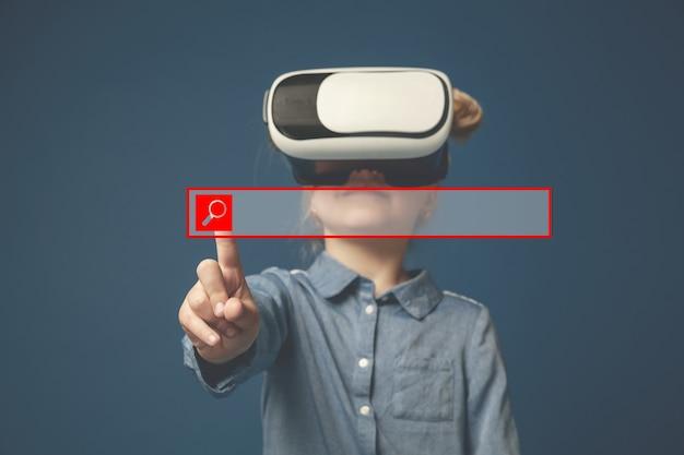 Hi-tech ist so nah. kleines mädchen oder kind, das auf die leere suchleiste mit vr-brille zeigt, die auf blauem studiohintergrund lokalisiert wird. speicherplatz kopieren. konzept der spitzentechnologie, videospiele, innovation.