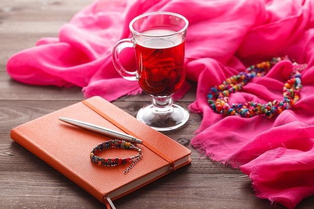 Hibiskus-tee und rosa seidenschal auf tisch