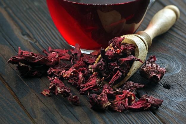 Hibiskustee. hibiskus-tee in einer holzschaufel und einer tasse frischem tee. vitamin tee gegen erkältung und grippe.