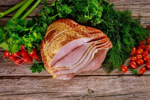 Hickory rauchte spiralförmig geschnittenen schinken mit frischem gemüse. feiertagsessen.