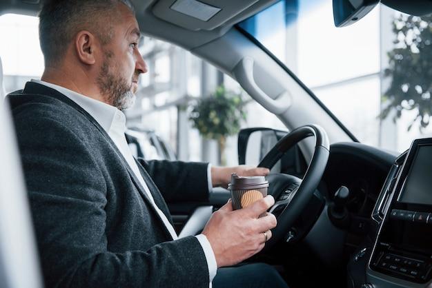 Hielt für eine pause an. seitenansicht des älteren geschäftsmannes in der offiziellen kleidung innerhalb des modernen autos