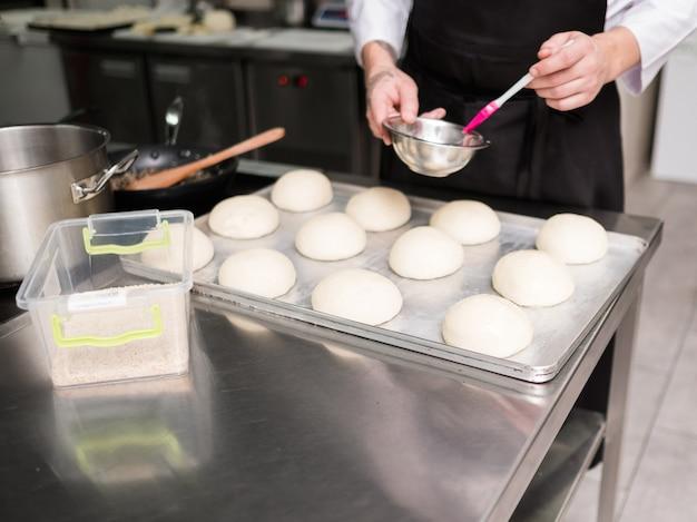 Hier beginnt ein burger. ein koch, der hamburgerbrötchen einfettet, bevor er sie in den ofen stellt und backt