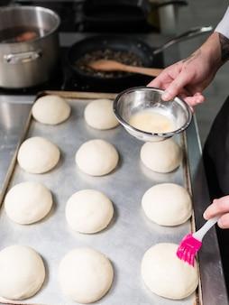 Hier beginnt ein burger. ein koch, der hamburgerbrötchen mit ei einfettet, bevor er sie in den ofen stellt und backt