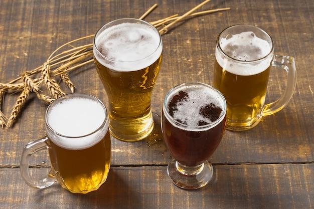 High angle bier in gläsern und pint mit schaum