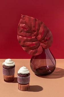 High angle blumen vase und cupcakes