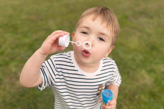 High angle boy spielt mit bubble blower