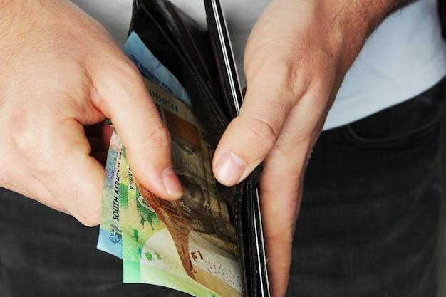 High angle closeup shot einer person, die etwas geld in eine lederbrieftasche steckt